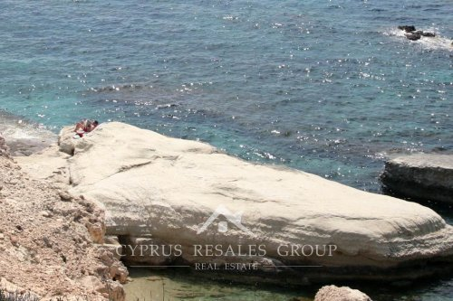 Reading morning paper on the rocks in Sea Caves, Cyprus